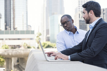 Two businessmen using laptop together - WESTF22640