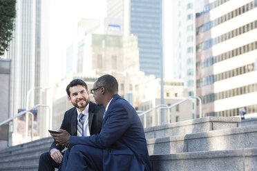 Two businessmen sitting on stairs talking and sharing tablet - WESTF22643