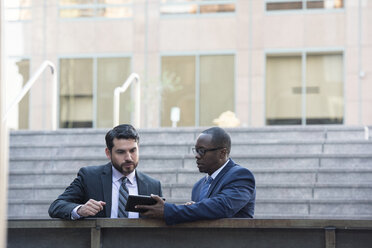 Two businessmen sharing tablet outdoors - WESTF22646