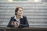 Businesswoman holding cell phone outdoors looking away - WESTF22649
