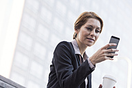 Smiling businesswoman holding cell phone and takeaway coffee - WESTF22652