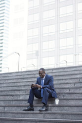 Businessman sitting on stairs with cell phone and takeaway coffee - WESTF22655