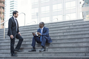 Two businessmen talking on stairs - WESTF22658
