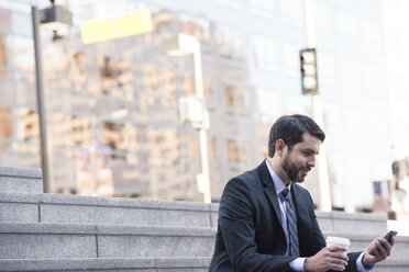 Businessman sitting on stairs with cell phone and takeaway coffee - WESTF22661
