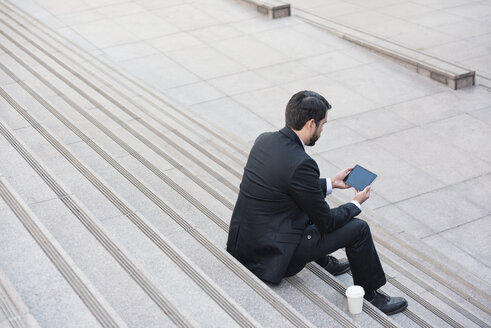 Businessman sitting on stairs with tablet and takeaway coffee - WESTF22664