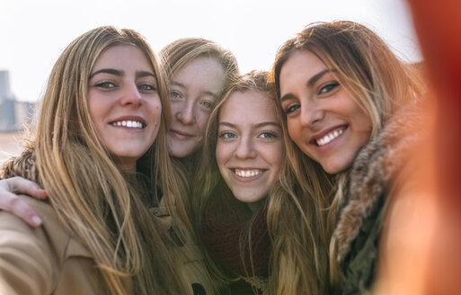 Portrait of four happy friends taking selfie - MGOF02921
