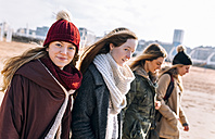 Portrait of teenage girl walking on the beach with her friends in winter - MGOF02924