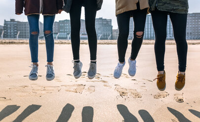 Legs of four friends jumping in the air on the beach - MGOF02930