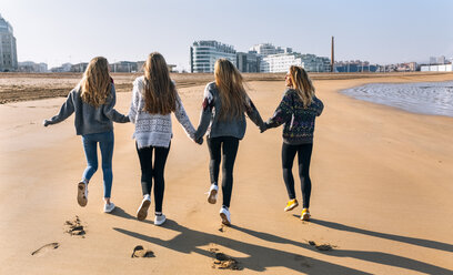 Spain, Gijon, back view of four friends running hand in hand on the beach - MGOF02939