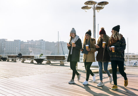 Four friends with coffee to go and cell phones walking on promenade in winter - MGOF02948
