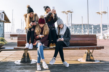 Four young women sitting on a bench using their cell phones - MGOF02951