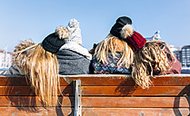 Back view of four friends sitting on a bench in winter - MGOF02954