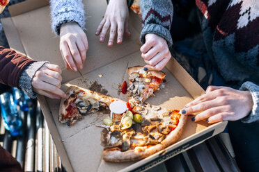 Four friends eating pizza outdoors, partial view - MGOF02960
