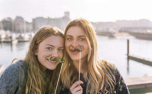 Portrait of two friends with toy moustaches - MGOF02963