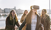 Teenage girl using wearing VR glasses while her friends watching her - MGOF02969