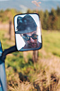 Reflection in rear-view mirror of man wearing a hat and sunglasses - WVF00837