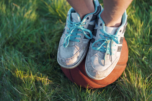 Person in sneakers standing on a basketball in a meadow - WVF00846