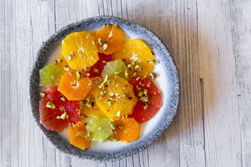 Plate of peeled and sliced citrus fruits with pistachios - SARF03179