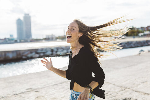 Exuberant young woman at the seafront - GIOF01827