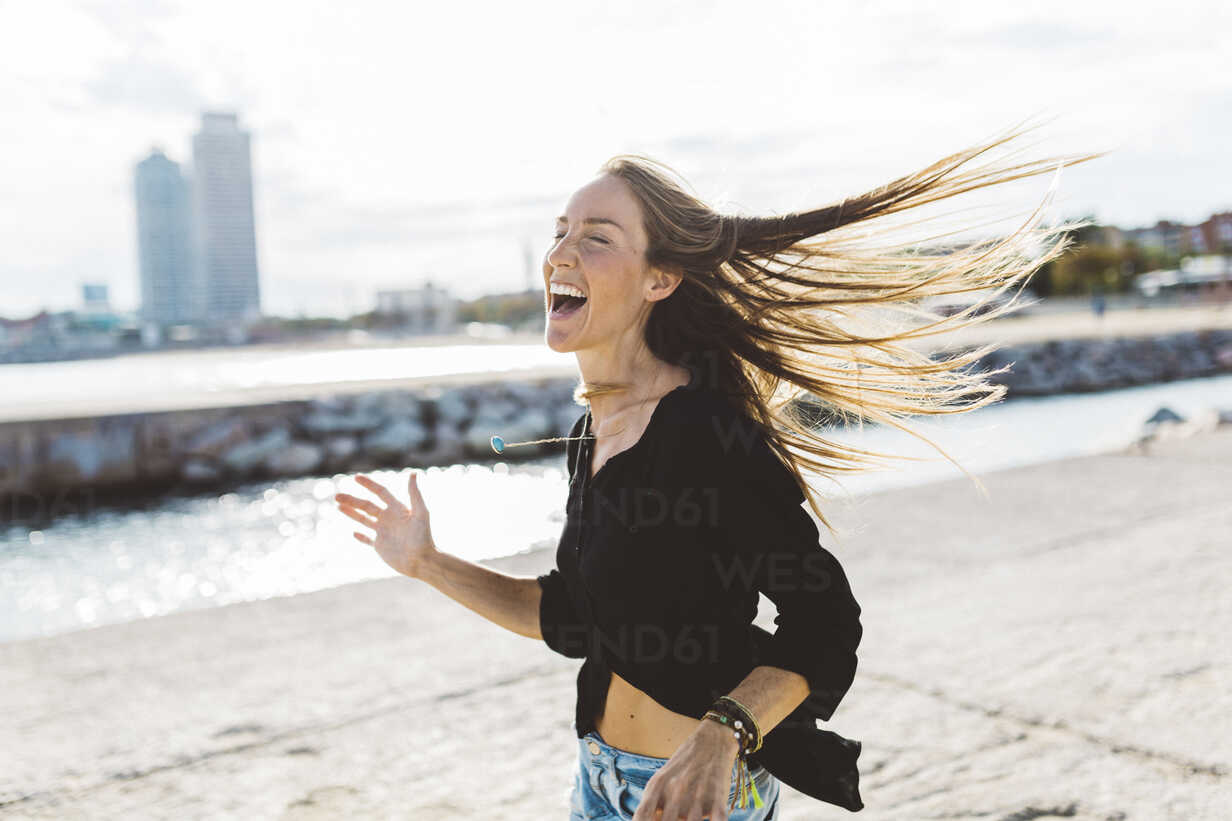 Exuberant young woman at the seafront - GIOF01827 - Giorgio Fochesato/Westend61