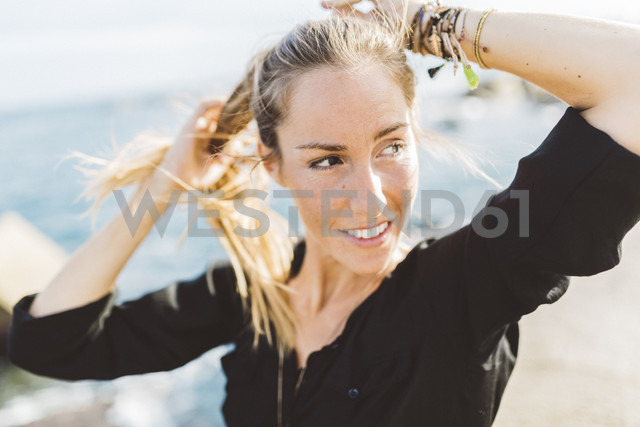 Smiling young woman at the seafront looking around - GIOF01830