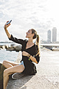 Young woman taking a selfie at the seafront - GIOF01833