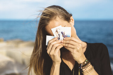 Young woman covering her face with instant photos of herself - GIOF01845