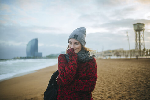 Spain, Barcelona, young woman on the beach in winter - KIJF01182