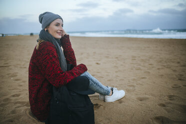 Smiling young woman sitting on the beach in winter - KIJF01188