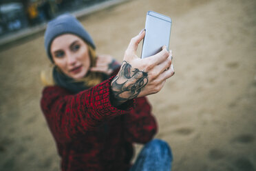 Close-up of tattooed woman's hand taking a selfie on the beach. - KIJF01191