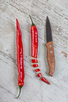 Whole and sliced red chili pod and a kitchen knife on wood - JUNF00830