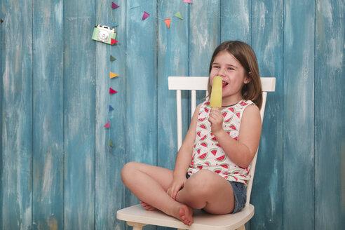 Happy little girl sitting on chair eating lemon ice lolly - RTBF00649