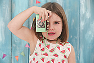 Portrait of little girl playing with vintage toy camera - RTBF00655