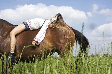 Girl with headphones  lying on horseback - FSF00780