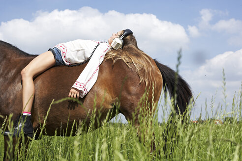 Girl with headphones  lying on horseback - FSF00780