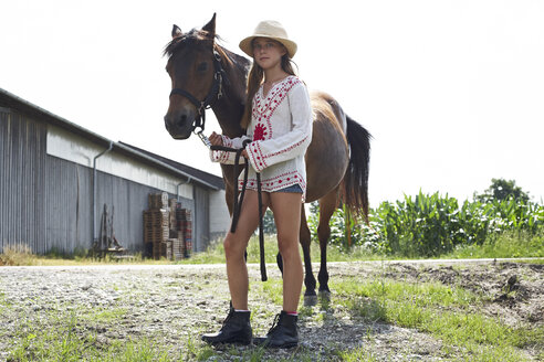 Girl standing with horse on farm - FSF00783