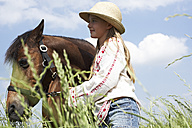 Smiling girl with horse on meadow - FSF00786