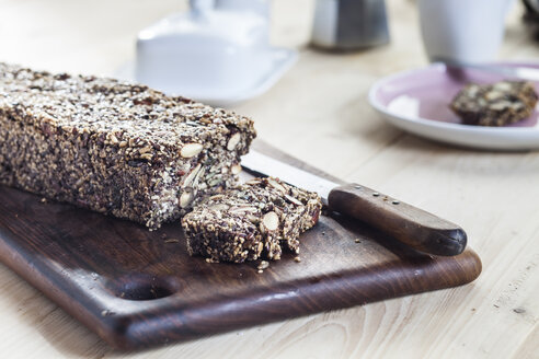 Home-baked wholemeal gluten-ree bread with nuts and seeds on wooden board - SBDF03152