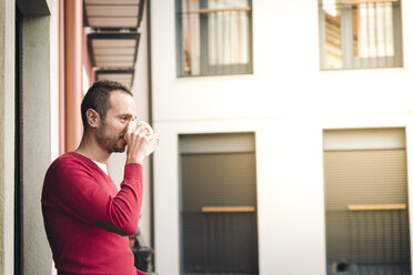 Man on balcony drinking coffee - EPF00330