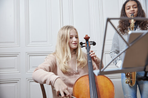 Two girls playing cello and saxophone together - RHF01807