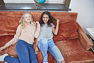 Two happy girls relaxing on couch - RHF01816