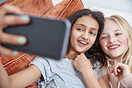 Two happy girls looking at smartphone - RHF01819