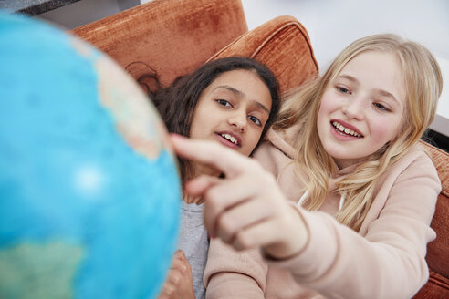 Two girls lying on couch pointing at globe - RHF01822