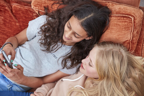 Two girls lying on couch using smartphone - RHF01831