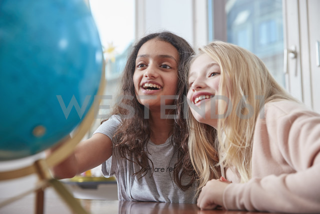Two excited girls looking at globe - RHF01837