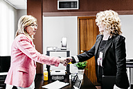Two businesswomen shaking hands in office - JRFF01189