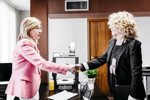 Two businesswomen shaking hands in office - JRFF01189