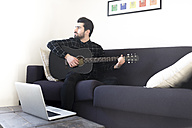 Young man at home sitting on couch playing guitar - FMOF00148