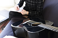 Guitar on couch and man taking notes - FMOF00151