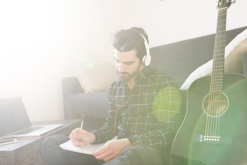 Young man at home with guitar wearing headphones and taking notes - FMOF00160